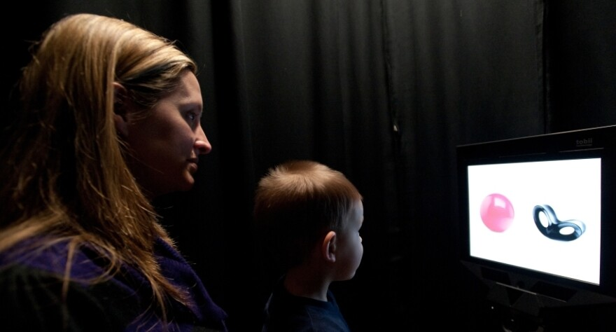Jackson Coles, 2, sits on the lap of his mother, Christy, and watches objects flash on a computer screen that also tracks his eye movement.