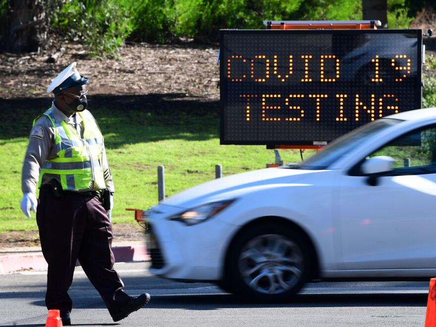 A traffic warden directs traffic as people arrive and depart from the coronavirus testing venue at Dodger Stadium in Los Angeles on Nov. 12. California surpassed more than 1 million confirmed coronavirus cases, according to Johns Hopkins University.