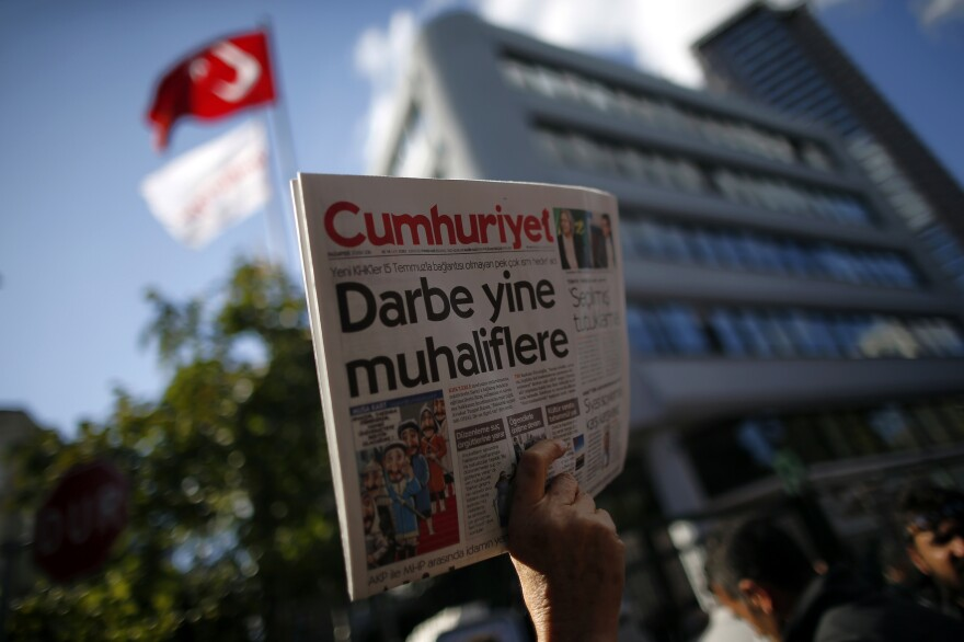 A man holds up the latest copy of Turkey's opposition <em>Cumhuriyet</em> newspaper outside its headquarters after Turkish police reportedly detained the chief editor and at least eight of its senior staff on Monday.