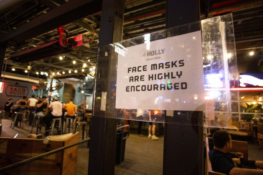 A sign at La Holly on East Sixth Street encourages patrons to wear face coverings.
