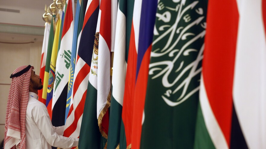 "A Saudi worker adjusts flags of participating countries before a meeting of energy ministers from OPEC and its allies in Jeddah, Saudi Arabia, on May 19. OPEC+ countries met again in Vienna on Monday and Tuesday and agreed to formalize their relationship in a ""Charter of Cooperation."""