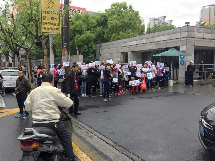 Investors in Zhongjin, a wealth-management company that collapsed this month, demonstrate outside a police office in Shanghai's Hongkou district, demanding repayment of their funds. Police later detained one of the demonstrators for distributing protest T-shirts.