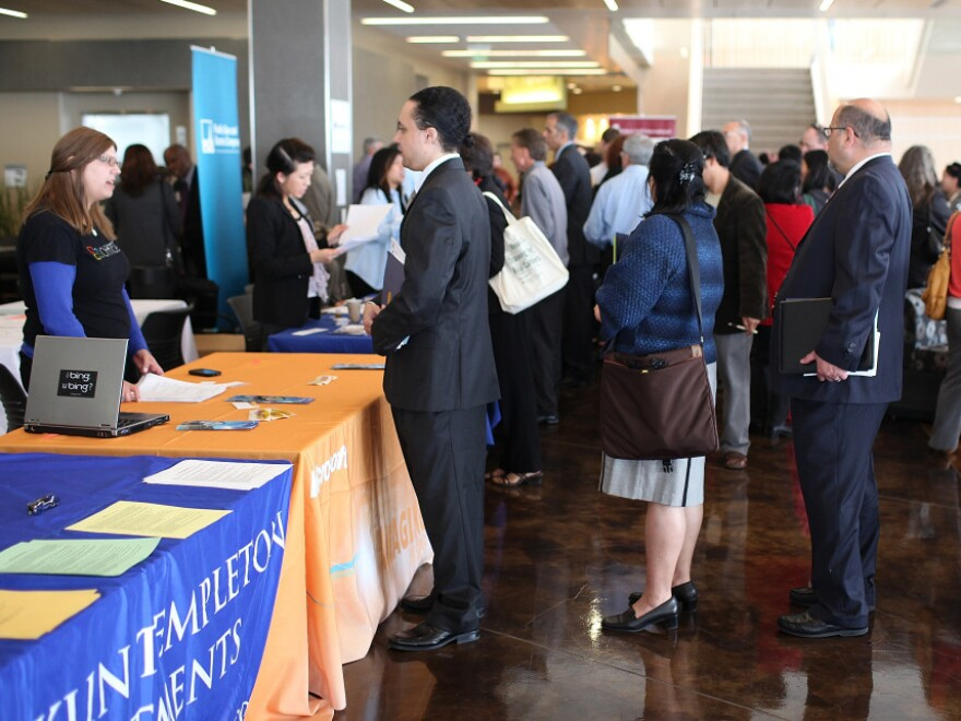 Job seekers wait in line to meet with recruiters during a job fair in San Mateo, Calif.