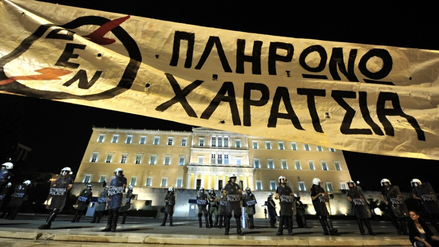 Demonstrators hold a banner protesting a new property tax, in front of the Greek Parliament building on Sunday.