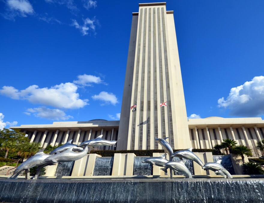 Florida Capitol with dolphin statues jumping in front of tall new capitol tower.