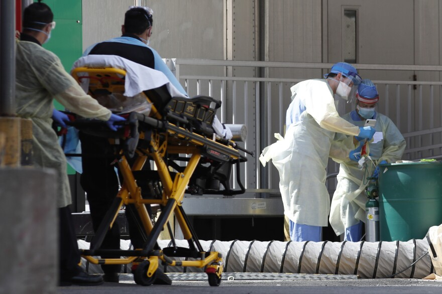 A patient is wheeled out of Elmhurst Hospital Center's emergency room on Tuesday, located within New York's Queens borough, an epicenter of the outbreak.