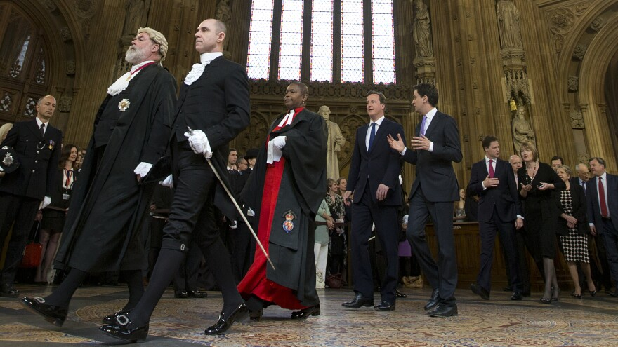 The Rev. Rose Hudson-Wilkin (center) walks in front of Britain's Prime Minister David Cameron and other lawmakers from the House of Commons through the central lobby toward the House of Lords for the state opening of Parliament, on May 8, 2013.