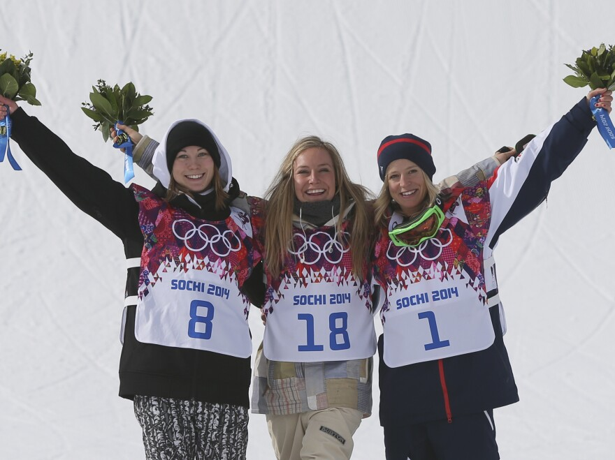Jamie Anderson of the United States, center, celebrates with silver medalist Enni Rukajarvi of Finland, left, and bronze medalist Jenny Jones of Britain, after Anderson won the women's snowboard slopestyle final at the 2014 Winter Olympics, on Sunday.