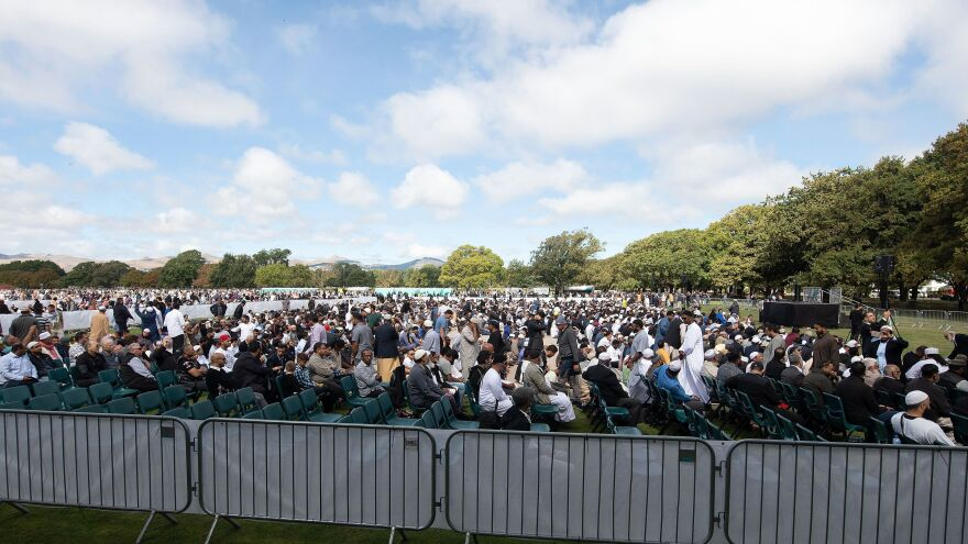 People listen to the call for prayer in Hagley Park in Christchurch, New Zealand, on Friday in memory of the victim of shooting attacks at two mosques one week earlier.