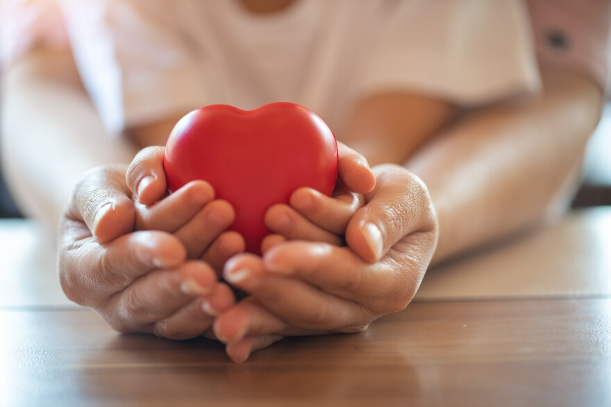 Adult and child hands holding red heart together. (Getty Images)