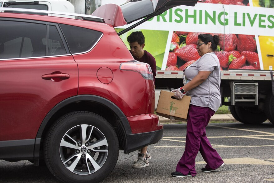 people loading boxes from a food bank into the back of a car