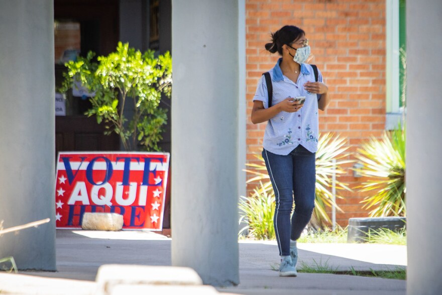 A woman wears a mask outside a polling place during the runoff elections on July 14.