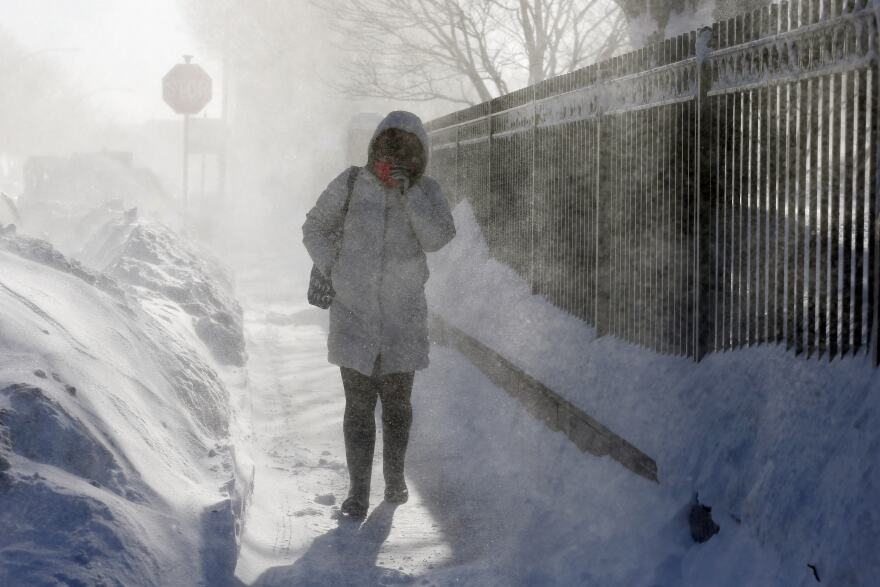 A woman walks through blowing snow in East Boston. New England remained bitterly cold Monday after the region's fourth winter storm in a month blew through.