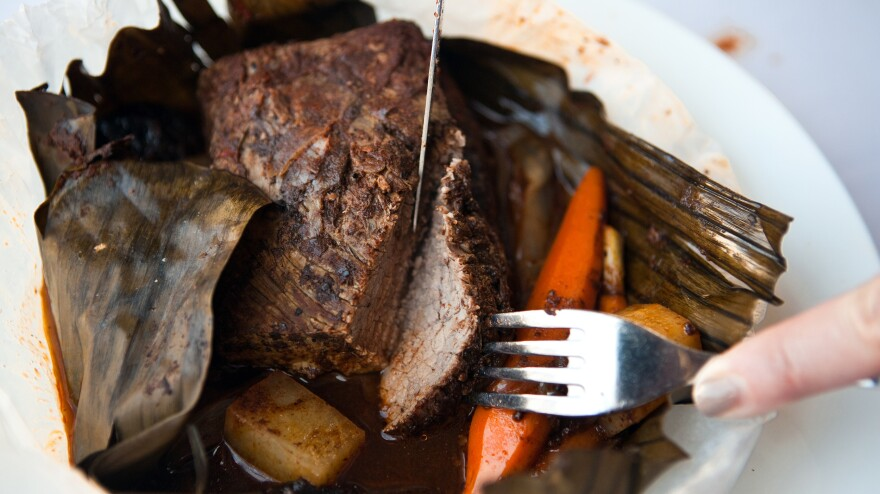 Roasted brisket of barbecued beef wrapped in banana leaf with dried fruit tzimmes, served with glazed baby carrots.