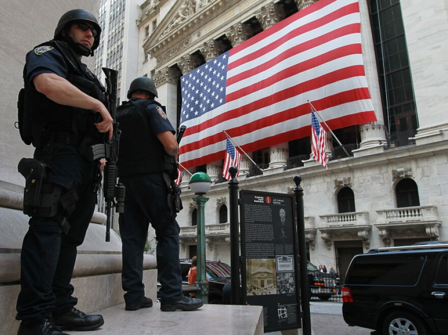 New York City policemen stand guard near the New York Stock Exchange on Friday. Security in New York and Washington has been stepped up based on what the government is calling a credible but unconfirmed threat of a possible car bomb attack.