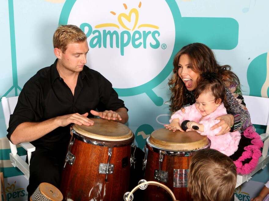 Latina pop star Thalía holds a toddler playing a <em>tumbadora</em> during a Pampers promotional event launching <em>Mi M<em>ú</em>sica, Mi Herencia</em> (My Music, My Heritage).