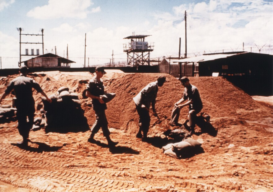 "Prisoners on work duty, filling sandbags in the ""Big Red"" work area."