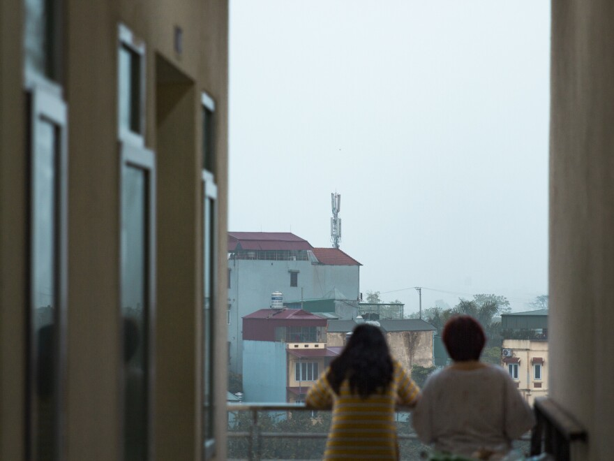 Residents of the quarantine center look out at the surrounding neighborhood.