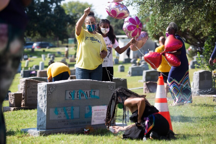People visit the graves of relatives whose headstones were vandalized at Evergreen Cemetery in East Austin during a Celebration of Live event Sept. 27.