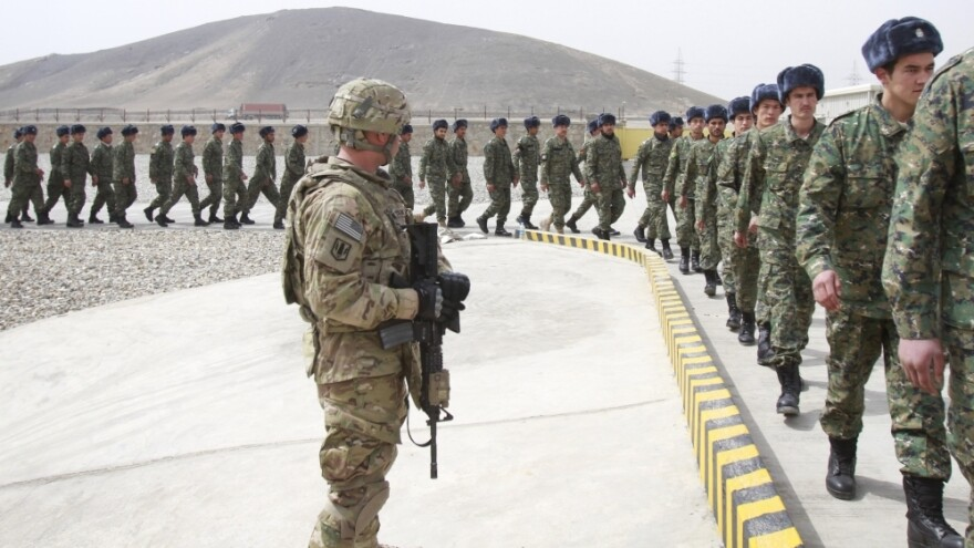 A U.S. soldier watches members of the Afghan Public Protection Force arrive at the transition ceremony on the outskirts of the Afghan capital Kabul on March 15. The APPF replaces all private security contractors in the country.