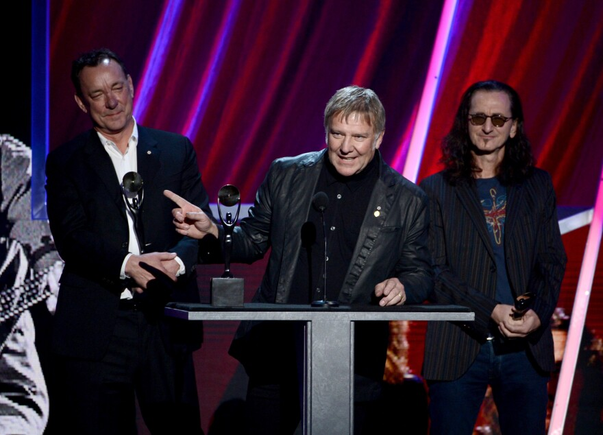 Alex Lifeson (center) with Neal Peart (left) and Geddy Lee at Rush's 2013 induction into the Rock and Roll Hall of Fame.