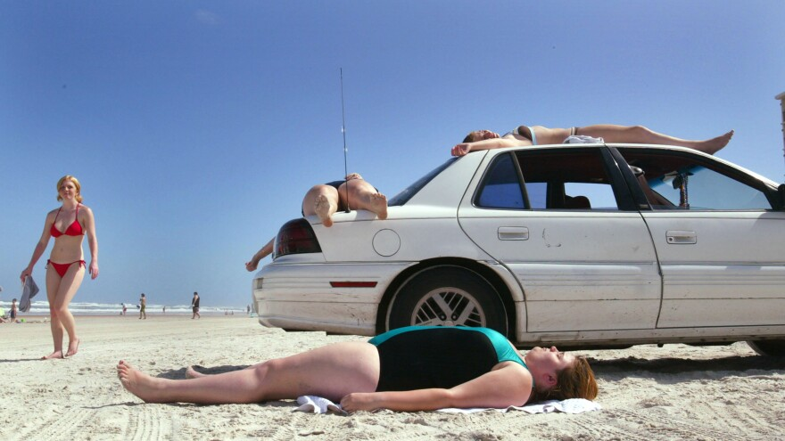 Vacationers lie on the beach, as well as their vehicle, as they sunbathe in Daytona during spring break. Only 17 miles of beach are currently open for car use and that number may soon be reduced.