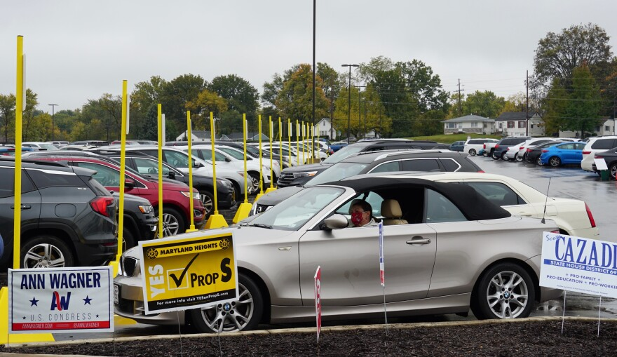 Rhonda Holstien waits in her car to vote curbside at the St. Louis County Board of Elections in St. Ann on Oct. 27. The yellow poles mark parking spots reserved for curbside voting.