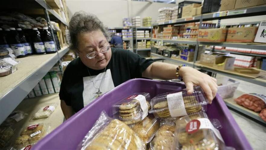 A volunteer unloads donated baked goods at a food bank in Des Moines, Iowa. Food banks could become strained, as more than 500,000 people could lose food stamps in 22 states reinstating work requirements this winter.