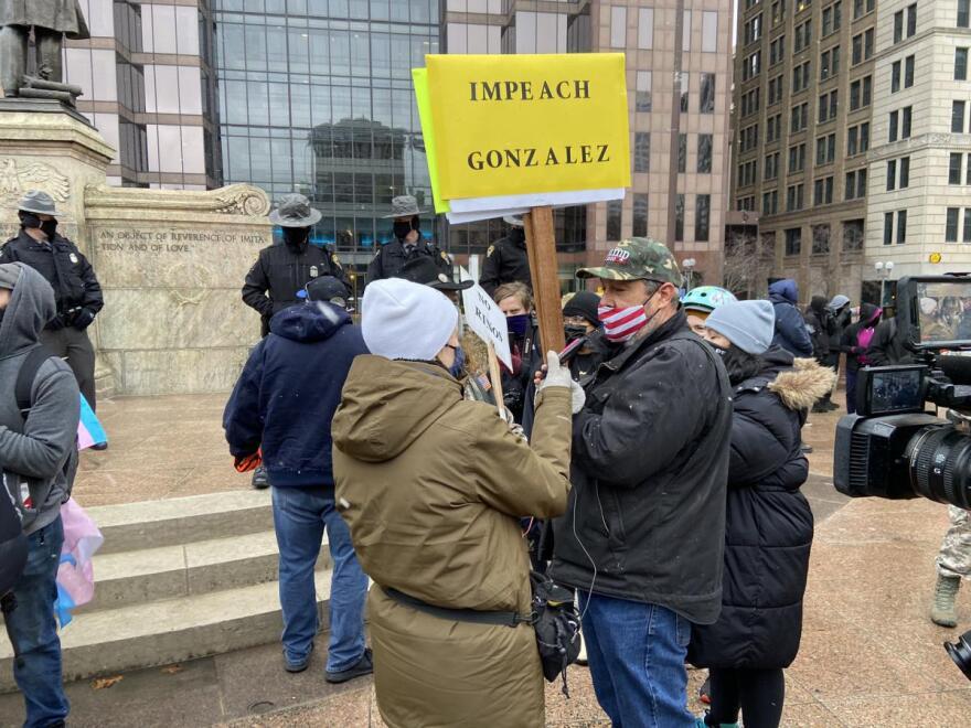 "man carrying ""Impeach Gonzalez"" sign"