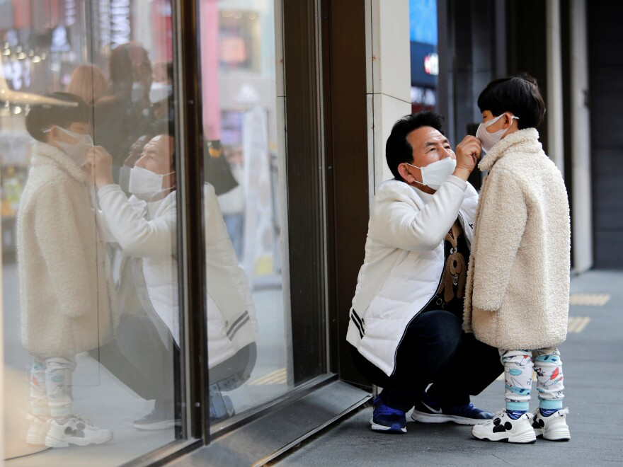 A man adjusts a boy's protective face mask on Thursday as they try to avoid contracting a new coronavirus in Seoul, South Korea. The country is reporting a spike in COVID-19 cases, predominantly in its south.