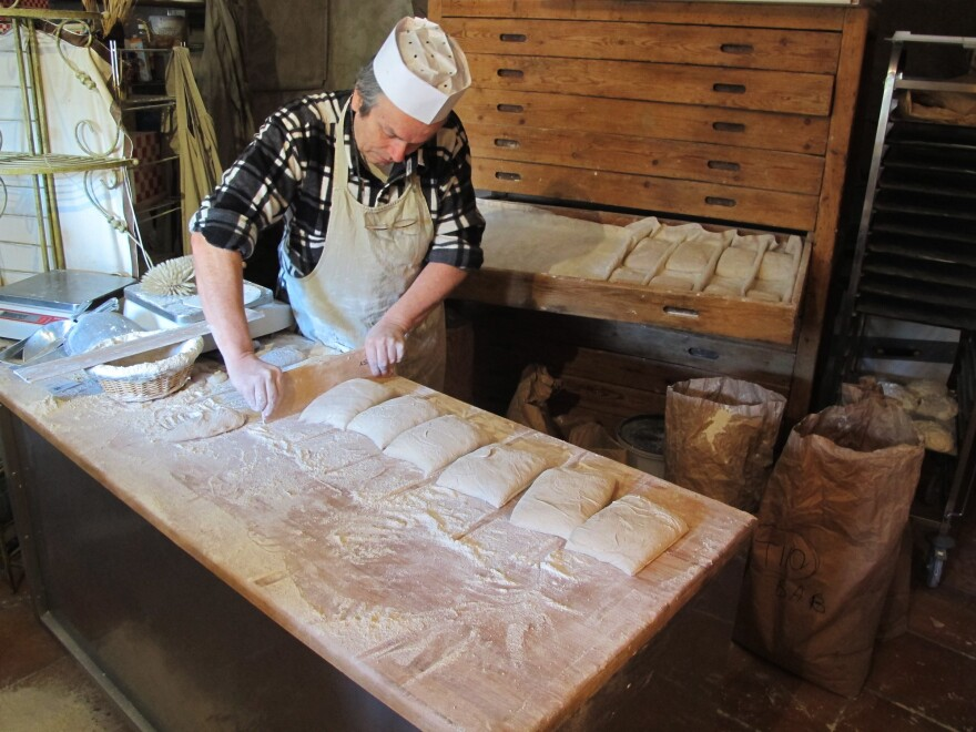 """Roland Feuillas of Cucugnan, France, is """"among a small movement <em>paysannes boulangers </em>(peasant bakers) who grow their own organic wheat, mill it into flour and make their bread,"""" Fromartz writes. Here, Feuillas shapes loaves with a single cut."""