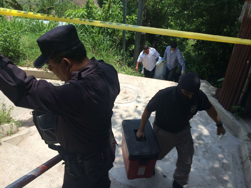 A police crime investigator, face covered to avoid retribution from gangs, clears a recent murder scene as a colleague holds up police tape and funeral home employees carry the body of the victim up the hill. The victim's widow suspects her husband was killed because he left a gang.
