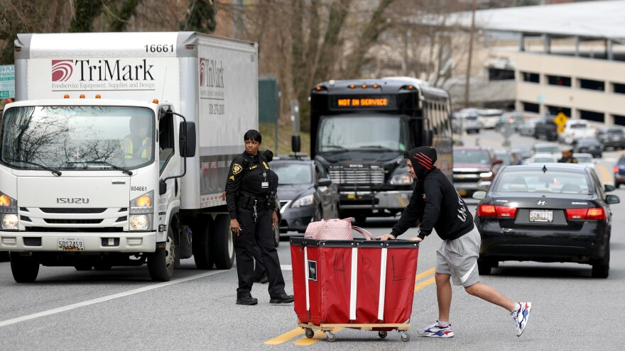 A Towson University student removes belongings out of the dorms as the school shut down days before the start of the scheduled spring break on March 11 in Towson, Maryland.