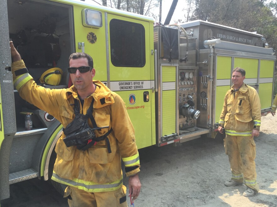 """Firefighters with a <a href=""""http://www.caloes.ca.gov/"""">California Office of Emergency Services</a> strike team take a break from mopping up hot spots on the Rocky Fire. Career firefighters working the blaze say they've never before seen a wildfire burn with such intensity and extreme behavior."""