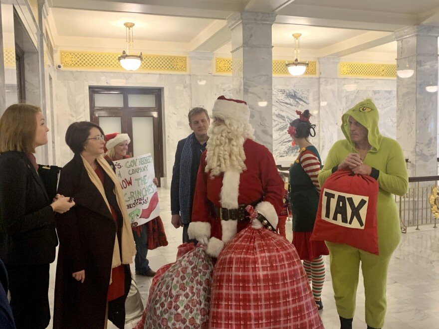 Photo of men dressed as Santa Claus and the Grinch inside Utah's Capitol building.