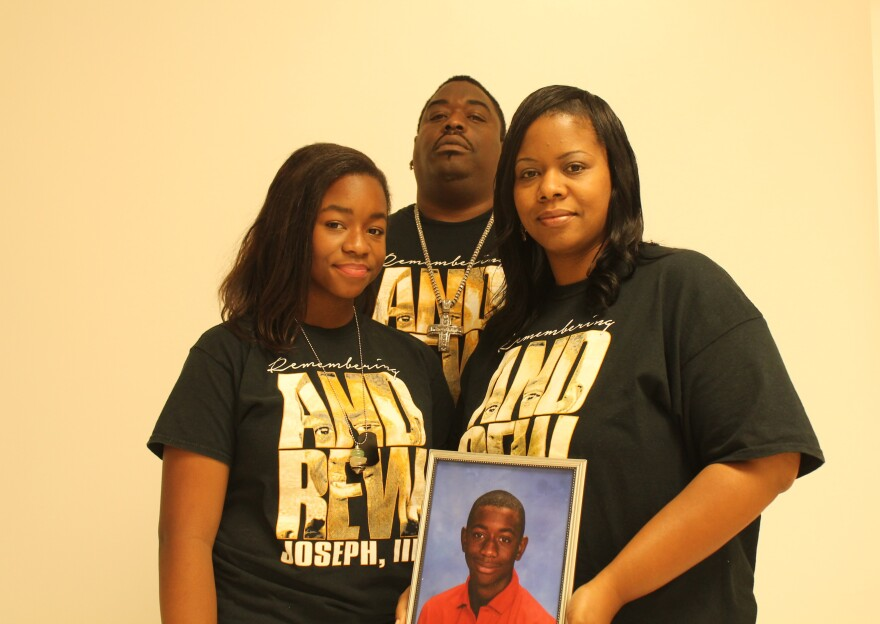 A mother and father pose with their daughter and a portrait of their son. They all wear black except for the boy in the photo who wears red.