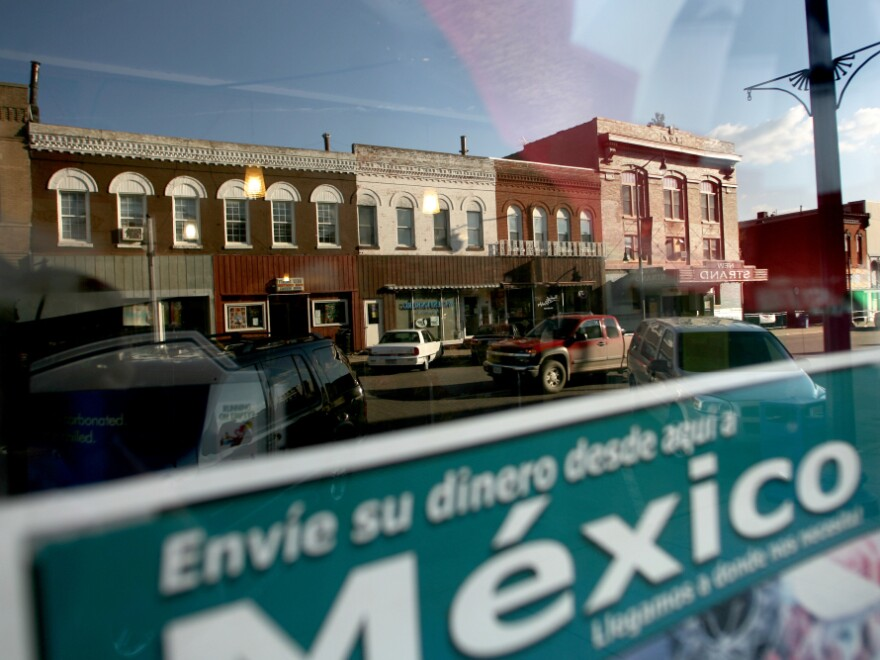 <p>Sending money to relatives in Mexico is a popular way for families to support each other. West Liberty's East 3rd Street is reflected in this window. </p>