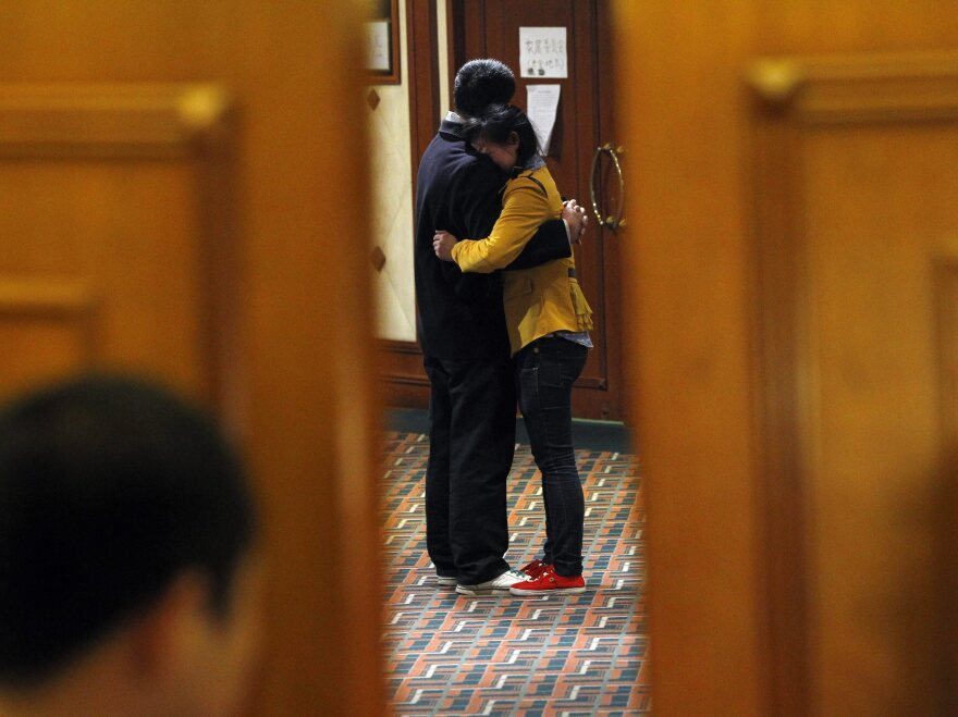 Relatives of passengers of the missing Malaysia Airlines flight MH370 embrace each other in a Beijing hotel after learning of news today that the flight ended in the southern Indian Ocean.