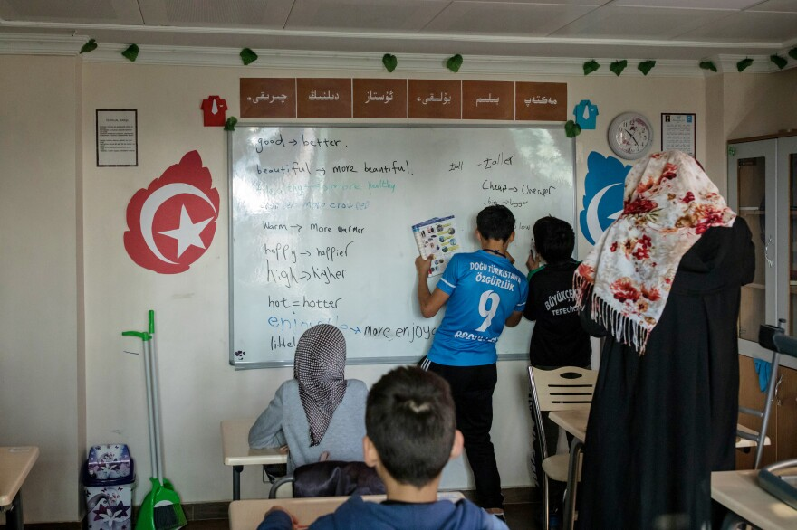 Students write on a whiteboard during English language class at the boarding school.