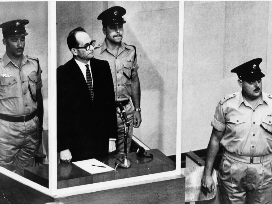 Adolf Eichmann, standing in a glass booth and flanked by guards, in the Jerusalem courtroom during his trial in 1961 for war crimes committed during World War II.