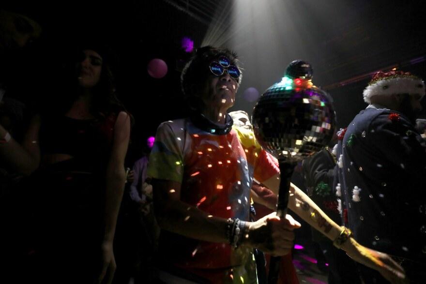 Yorkie Louie on the dance floor with a disco ball scepter.