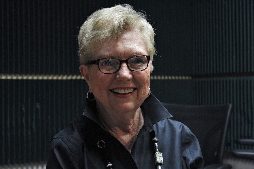 Image of a Kay Barnes, a woman with white hair, against a dark background.