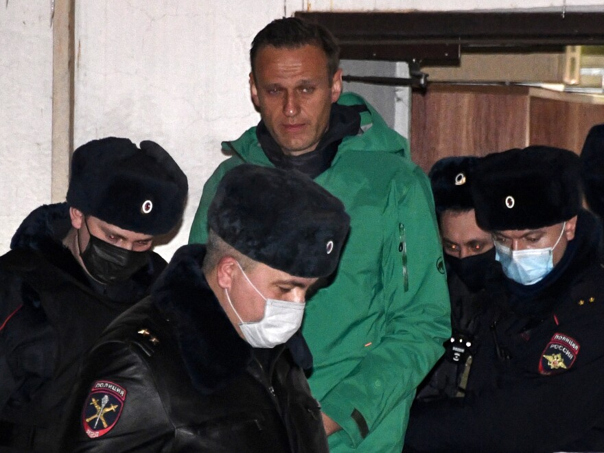 Opposition leader Alexei Navalny is escorted out of a police station in Khimki, outside Moscow, following the court ruling that ordered him jailed for 30 days.