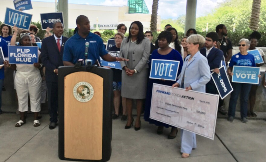 Andrew Gillum presents a check to Florida Democratic Party Chair Terrie Rizzo for voter registration efforts.