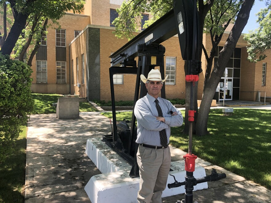 Andrews County Judge Charlie Falcon stands in front of the courthouse. His community, which depends heavily on the oil and gas industry, is making tough decisions right now.