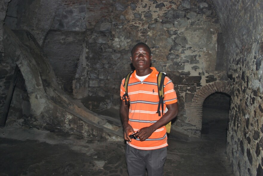 George Mwinnyaa stands in a slave castle dungeon for male captives in Ghana.
