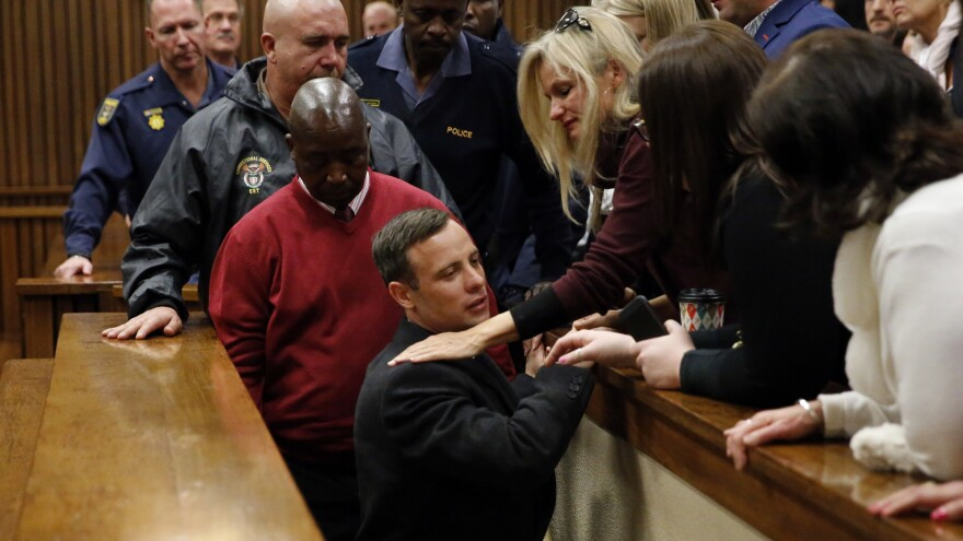 Oscar Pistorius is embraced by family members as he leaves the High Court after being sentenced to six years in prison for the 2013 murder of his girlfriend.