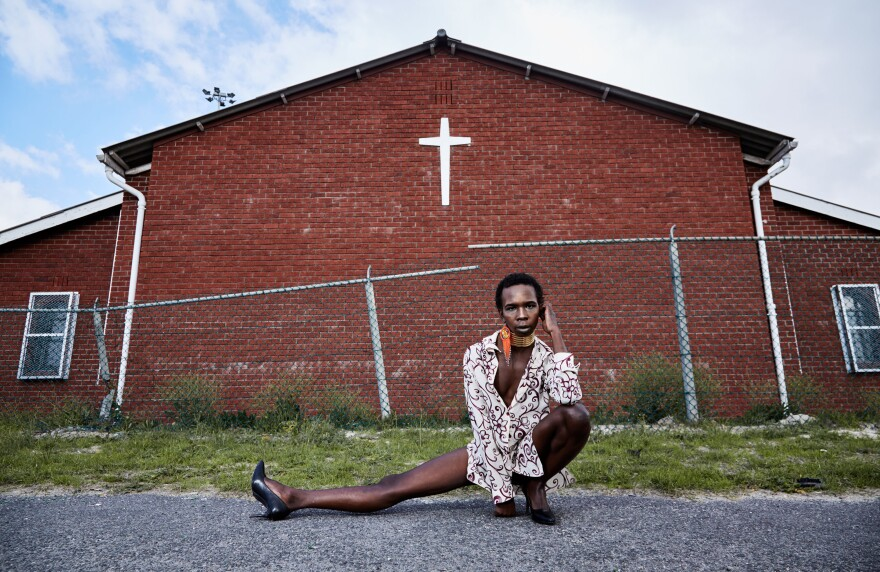 "Mandisi Dolle Phika, 27, asked to be photographed by a church, an important place to her family but a place where she says she has faced anti-queer bias. At Catholic school, she remembers, ""I once overheard a conversation where it was said I have a 'gay-demon.'"" Now studying LGBTQI political leadership, she believes in ""a colorful God"" that ""celebrates diversity in all its manifestations."""