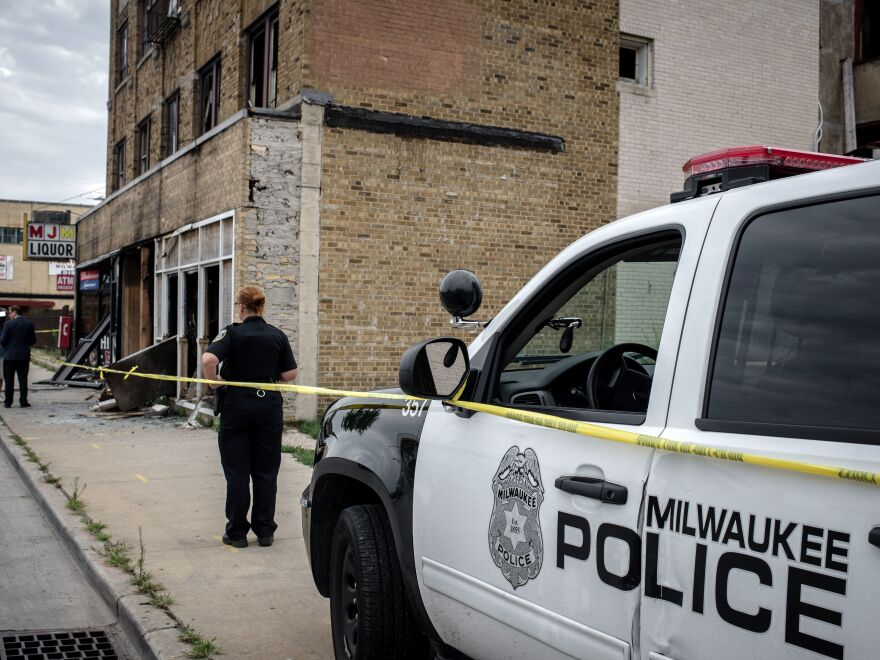 A Milwaukee police officer stands before the remains of a bar last summer, after police there faced off with protesters following the police shooting of a black man. For decades, interactions between police and people of color in the Midwestern city have been fraught, and those encounters are the subject of a new lawsuit brought by the ACLU.