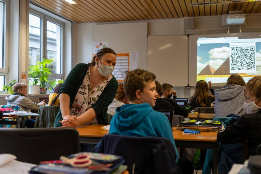 Teacher Inga Deppa works with students in an English class at Jacobishule in Kalletal, Germany, on Oct. 7, 2020. Masks were optional for students when they were seated at their desks, but the regional health authority has since tightened mask rules for older students.